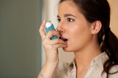 An asthmatic woman is holding an inhaler.
